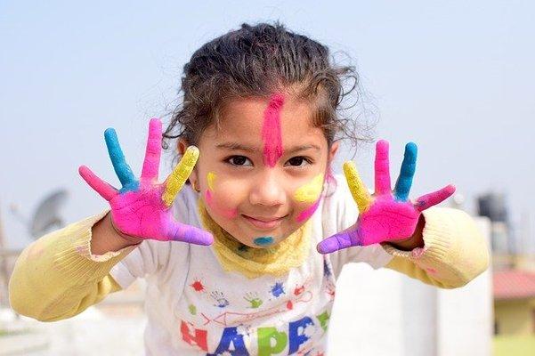 Kleines Mädchen mit Farbe an den Händen und im Gesicht.