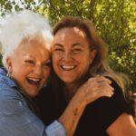 Bild von zwei Frauen, die fröhlich sind und sich umarmen.