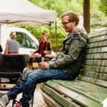 Mann der auf einer Bank sitzt. Neben ihm steht ein Rollstuhl