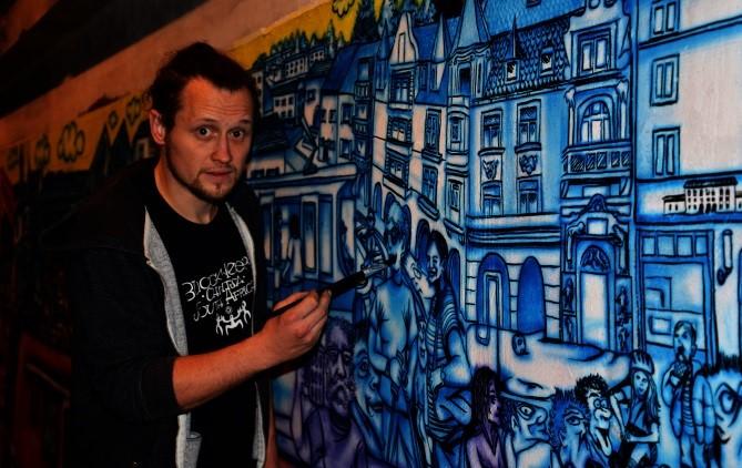 Foto vonKünster Martin Blumöhr vor einem Graffiti
