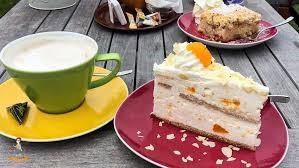 Foto von einem Stück Kuchen und einer Tasse Kaffee auf einem Tisch.
