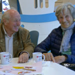 Zwei ältere Personen sitzen mit einer Kaffeetasse am Tisch.