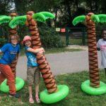 Drei Kinder die im Park an aufblasbaren Palmen stehen